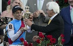 Trainer Bob Baffert hands the winner's trophy to jockey John Velazquez after their victory with Medina Spirit in the 147th running of the Kentucky D
