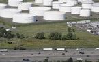 FILE - In this Sept. 8, 2008 file photo traffic on I-95 passes oil storage tanks owned by the Colonial Pipeline Company in Linden, N.J. A major pipeli