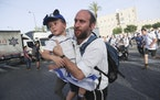 Israelis run to shelters as air attack sirens goes off during a Jerusalem Day march, in Jerusalem, Monday, May 10, 2021. Explosions have been heard in