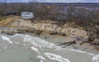 In this Dec. 4, 2019, photo, erosion reaches a house along Lake Michigan's southwestern shoreline in Stevensville, Mich. A months-long spell of dry,