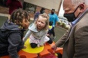 Gov. Tim Walz talked to children on the playground at the Wilder Child Development Center in St. Paul after holding a press conference there. LEILA NA