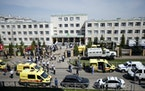 Ambulances and police cars and a truck are parked at a school after a shooting in Kazan, Russia, Tuesday, May 11, 2021. Russian media report that seve