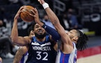 Timberwolves center Karl-Anthony Towns attempts a layup as Detroit center Jahlil Okafor defends during the first half