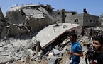 People inspect the rubble of a destroyed residential building which was hit by Israeli airstrikes, in Gaza City, Wednesday, May 12, 2021.