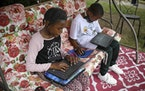 Fourth-grader Sammiayah Thompson, left, and her brother, third-grader Nehemiah Thompson, worked outside in their yard in June 2020 on laptops provided