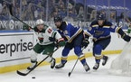 The Wild's Jared Spurgeon battles St. Louis Blues' Zach Sanford and Mackenzie MacEachern for the loose puck in the second period