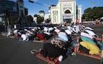 Muslim men pray on a street outside a crowded Al Mashun Great Mosque during an Eid al-Fitr prayer in Medan, North Sumatra, Indonesia, Thursday, May 13