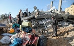 People gather items from the rubble of a residential building in Gaza City, Gaza Strip, Thursday, May 13, 2021, that was destroyed by an Israeli airst