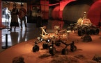 Visitors pass by an exhibition depicting rovers on Mars in Beijing on Friday, May 14, 2021. China says its Mars probe and accompanying rover are to la