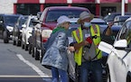A customer helps pumping gas at Costco, as other wait in line, on Tuesday, May 11, 2021, in Charlotte, N.C. Colonial Pipeline, which delivers about 45