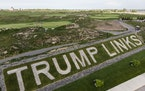 Patrons play the links as a giant branding sign is displayed with flagstones at Trump Golf Links at Ferry Point in the Bronx borough of New York on Tu