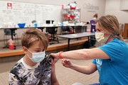 Maddox Nichols, 13, of Minneapolis, got his first dose of the Pfizer COVID-19 vaccine from nurse Erin Oleson last month at Children's Minnesota. ] A