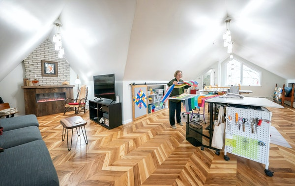 Carolyn Davidson worked at the cutting table of her new quilting room. Her husband, Dennis Davidson, laid the distinctive wood floor using reclaimed l