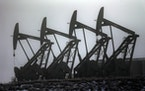 Shown are oil pump jacks in Williston, N.D. Northern Oil and Gas is buying assets that include wells in North Dakota.