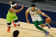 Boston Celtics forward Jayson Tatum (0) drives on Minnesota Timberwolves forward Josh Okogie (20) in the first quarter during an NBA basketball game,