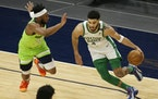 Boston Celtics forward Jayson Tatum (0) drives on Minnesota Timberwolves forward Josh Okogie (20) in the first quarter during an NBA basketball game,