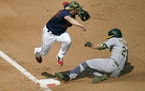 Minnesota Twins third baseman Josh Donaldson, leaps clear of Oakland Athletics' Stephen Piscotty, right, as Piscotty advances to third from second