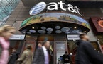 FILE - In this Oct. 21, 2014 file photo, people pass an AT&T store in New York's Times Square. AT&T will combine its media operations that include C