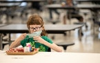 A child puts her mask back on after finishing lunch at a socially distanced table in the cafeteria of Medora Elementary School on March 17, 2021 in Lo