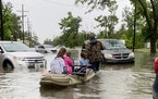 Parents use boats to pick up students from schools after nearly a foot of rain fell in Lake Charles, La., Monday, May 17, 2021.