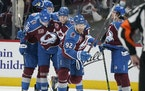 Avalanche left wing Gabriel Landeskog, front, celebrated with teammates after scoring a goal against the Blues in the third period Monday.