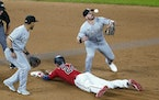 Chicago White Sox second baseman Danny Mendick, right, cannot handle the throw as Minnesota Twins' Trevor Larnach (24) doubles in the eighth inning