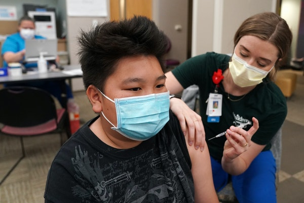 Kuabcag Yang, 13, of Brooklyn Park got his first dose of the Pfizer COVID-19 vaccine from nurse Jenn Doble Thursday at Children's Minnesota.
