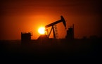 The sun set over the Bakken Oil Formation, behind an oil well near Williston, N.D., in 2013.