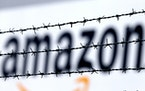 FILE - In this Feb. 19, 2013 file photo, the internet trader Amazon logo is seen behind barbed wire at the company's logistic center in Rheinberg, G