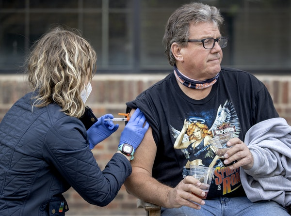 Mike Hogan, 63, of Fridley held two beers as he received a COVID-19 vaccine from physician assistant Laura Willson at Lake Monster Brewing last week i