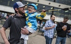 Austin Erickson and his son Jake dressed in his favorite jockey Victor Espinoza's colors cheered for the horses in the second race.