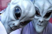 """Two """"aliens"""" pose for a photograph in front of Imagine That Scrapbooks on Main Street in downtown Roswell, N.M., Friday, July 6, 2007, during the"""