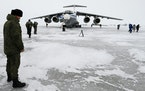 A Russian officer stands near a landed Il-76 military cargo plane on the Alexandra Land island near Nagurskoye, Russia, on May 17. Once a desolate hom