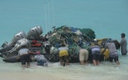 One big hazard of single-use plastic is what it is doing to marine life. This April 10 photo shows workers with the Papahanaumokuakea Marine Debris Pr