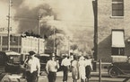 Two armed men walk away from burning buildings during the Tulsa Race Massacre in 1921.
