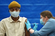 Savior Allen-Knight, a recent Hamline University graduate, got the COVID-19 vaccine from pharmacist Karla Marz at a free vaccination event May 20 at H
