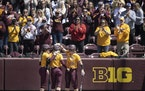 Gophers outfielder Natalie DenHartog celebrated one of her 15 homers this season with Emily Hansen, left, and Katelyn Kemmetmueller.