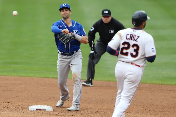 The Royals' Whit Merrifield threw to first after forcing out the Twins' Nelson Cruz to complete a double play in the fifth inning Sunday.
