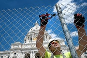 Tim Gasner of Keller Fence cut, rolled and carried away some of the 2,300 feet of chain link fence that has protected the State Capitol for the last y