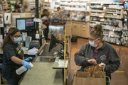 Cindy Lambing of Minneapolis completed her shopping at Linden Hills Co-op in Minneapolis last spring as cashier Sareena Tippett sanitized the checkout