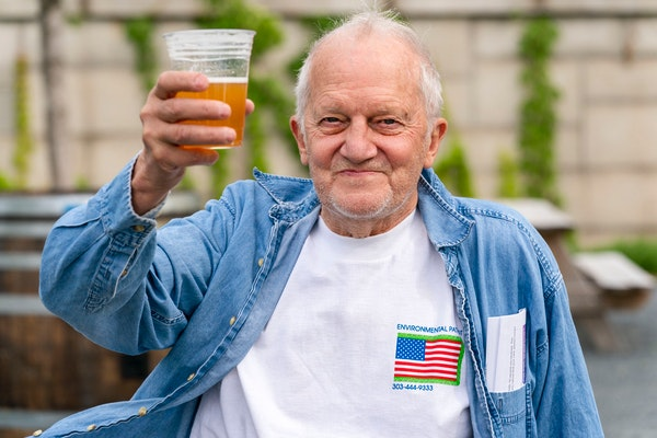 In this May 6, 2021 photo, George Ripley, 72, of Washington, holds up his free beer after receiving the J&J COVID-19 vaccine shot, at The REACH at the