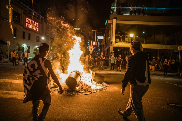 Protesters set a dumpster on fire and added other items to it late Thursday night in Minneapolis' Uptown neighborhood.