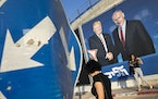 People walk by an election campaign billboard that shows Israeli Prime Minister Benjamin Netanyahu, right, and then-President Donald Trump, in Tel Avi