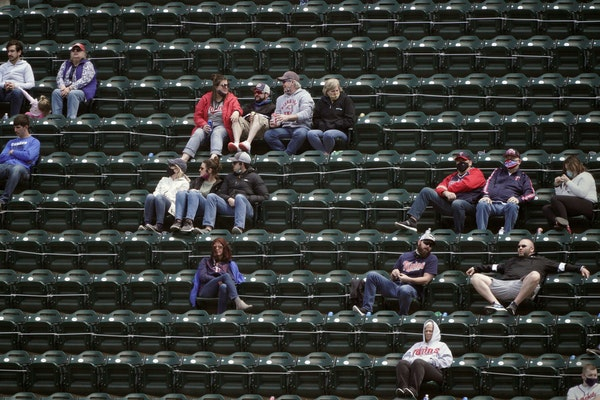 Twins fans eager for warmer weather and the pandemic's end enjoy some outdoor fun while rooting on the home team at a recent game at Target Field. ]