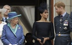 In this 2018 photo, Britain's Queen Elizabeth II, Meghan the Duchess of Sussex and Prince Harry stand on a balcony to watch a flyover of Royal Air F