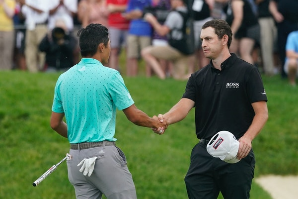 Patrick Cantlay, right, shakes hands with Collin Morikawa after Cantlay won the Memorial golf tournament