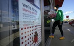 A passerby walks past a hiring sign while entering a Target store in Westwood, Mass., in September 2020.