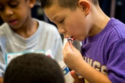 First-grader Kevin Nielson rubbed an ice cube on his lips in his un-air-conditioned classroom at Hiawatha Elementary in 2013. Hiawatha is one of 15 Mi