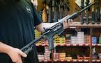 An employee holds an AR-15 style rifle inside Clark Brothers Gun Shop in Warrenton, Va., Feb. 25, 2018.