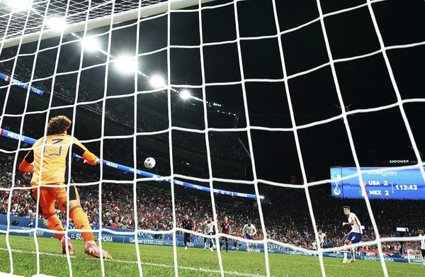 Christian Pulisic (10) of the U.S. national team scores a penalty kick goal against Mexico's Guillermo Ochoa in extra time at the CONCACAF Nations L